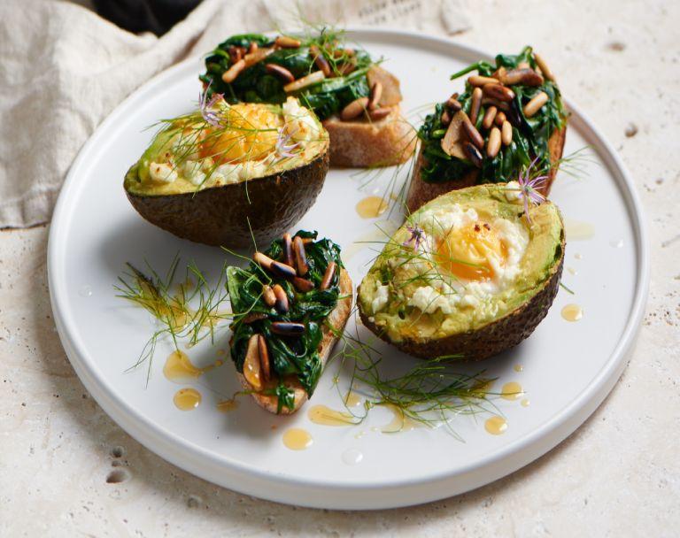 Zapiekane awokado z jajkiem z młodym szpinakiem, pomidorami i serem pleśniowym